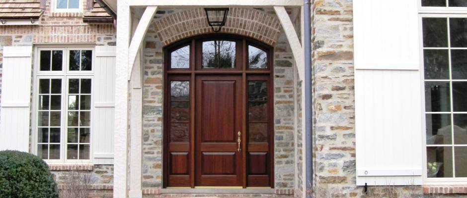 Custom wood entry door with sidelites and arched transom.